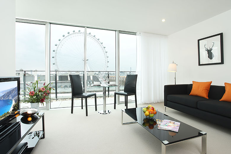 A bright, modern lounge with views of the London Eye